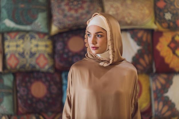 カフェに座っているアラビアの若いイスラム教徒の女性。