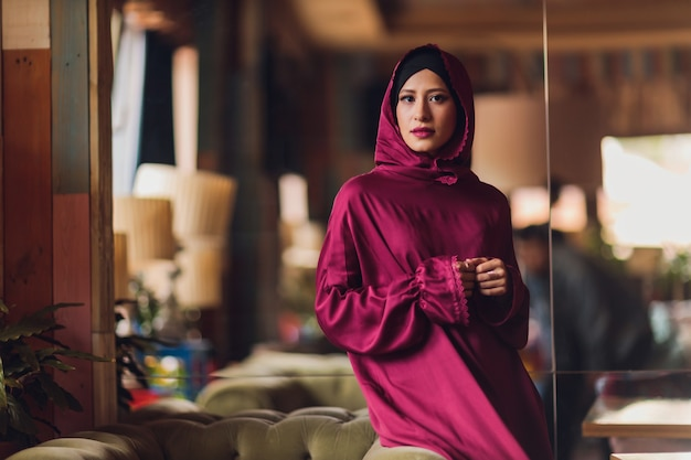 Арабская молодая мусульманская женщина, сидящая в кафе