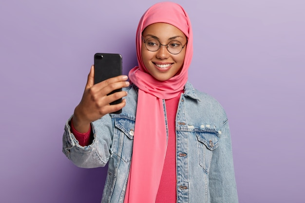 Arabian young woman with cheerful expression, wears round spectacles, makes video call via cellular