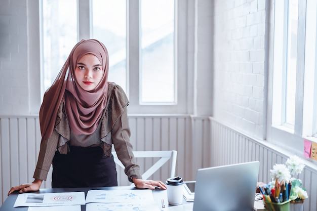 Arabic business woman in brown hijab at office workplace.