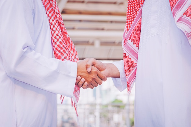 Arabic businessman giving an handshake to his business partner, on construction site