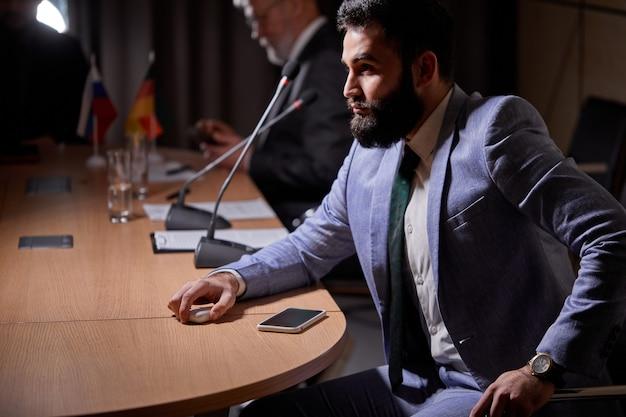 話者の報告に注意深く耳を傾け、会議室の机に座って、ネクタイなしで会議をしているスーツを着たアラビア人ビジネスマン。ビジネス、エグゼクティブの人々の概念