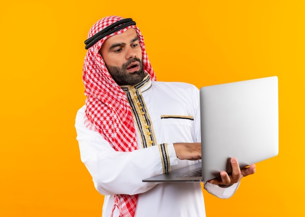 Арабский бизнесмен в традиционной одежде, держащий ноутбук, выглядит удивленным и пораженным, стоя над оранжевой стеной