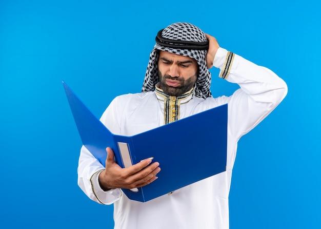 파란색 벽 위에 서있는 머리에 손으로 혼동 그것을보고 오픈 폴더를 들고 전통적인 착용 아랍어 사업가