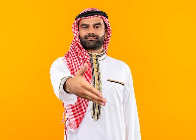 오렌지 벽 위에 서있는 손을 제공하는 자신감 인사를 찾고 전통적인 착용 아랍어 사업가