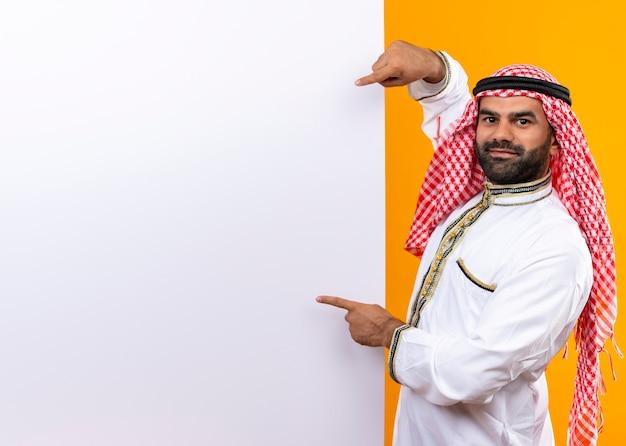 オレンジ色の壁の上に立って自信を持って見える空白の看板を指して伝統的な服を着たアラビアのビジネスマン