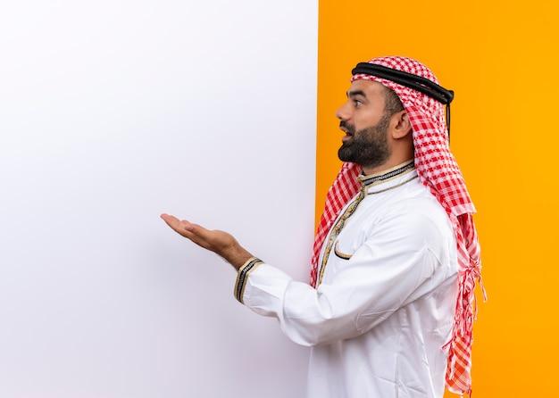 오렌지 벽 위에 서 놀란 팔을 찾고 빈 광고판에서 가리키는 전통적인 착용 아랍어 사업가