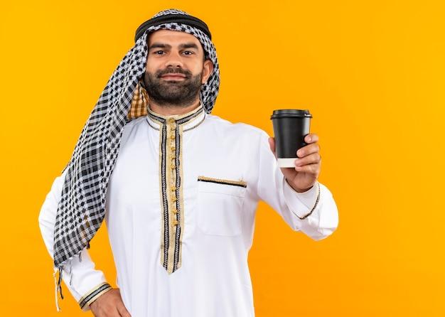 オレンジ色の壁の上に立っている顔に自信を持って笑顔でコーヒーカップを示す伝統的な服を着たアラビアのビジネスマン