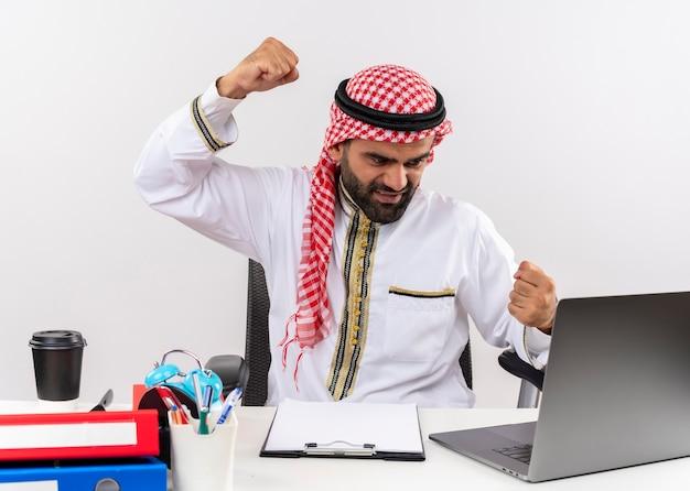 사무실에서 일하는 화난 얼굴로 주먹을 떨리는 노트북 컴퓨터와 함께 테이블에 앉아 전통적인 착용 아랍어 사업가