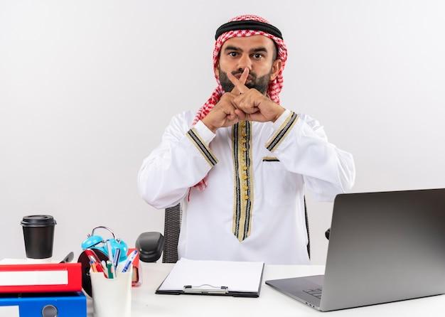 사무실에서 침묵 제스처를 만드는 노트북 컴퓨터 횡단 검지 손가락으로 테이블에 앉아 전통적인 착용 아랍어 사업가