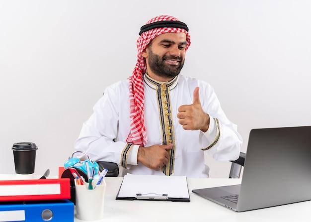 노트북 컴퓨터와 함께 테이블에 앉아 전통적인 착용 아랍어 사업가 행복하고 긍정적 인 미소를 보여주는 엄지 손가락 사무실에서 작업