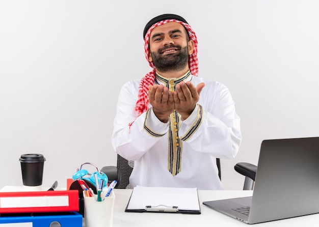 一緒に手をつないでテーブルに座ってオフィスで働くお金を求めて伝統的な服を着たアラビアのビジネスマン