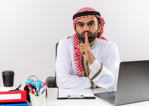 Арабский бизнесмен в традиционной одежде, сидя за столом с портативным компьютером, делая жест молчания с пальцем на губах, работая в офисе