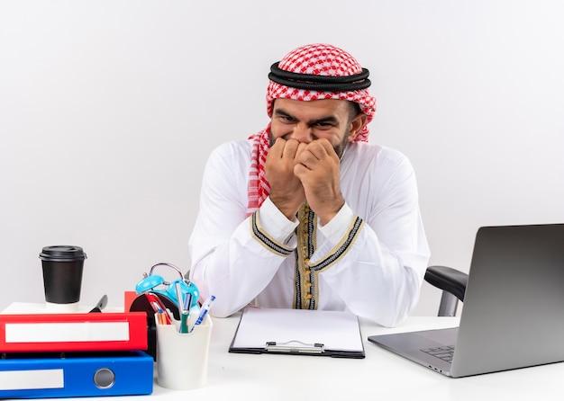 ラップトップコンピューターでテーブルに座ってストレスと神経質にオフィスで働いている彼の爪を噛む伝統的な服を着たアラビアのビジネスマン