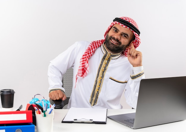 사무실에서 일하는 얼굴에 큰 미소로 노트북 컴퓨터와 함께 테이블에 앉아 전통적인 착용 아랍어 사업가