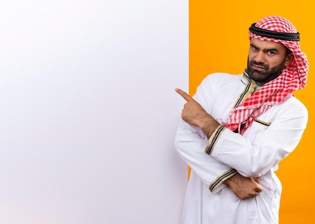 オレンジ色の壁に怒った顔でそれを指で指している空白の看板の近くに立っている伝統的な服を着たアラビアのビジネスマン