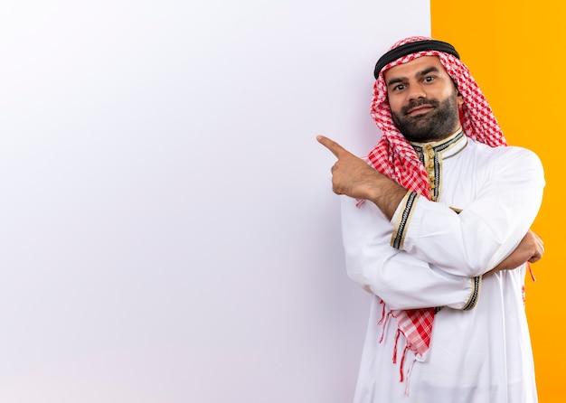オレンジ色の壁の上の顔に自信を持って笑顔でそれを指で指している空白の看板の近くに立っている伝統的な服を着たアラビアのビジネスマン