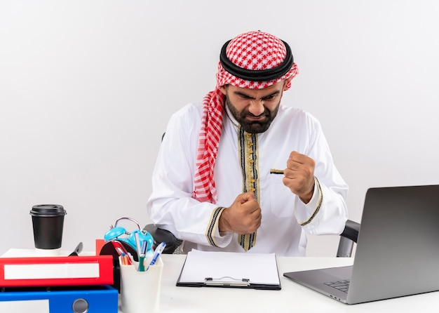 공격적인 표정으로 주먹을 떨리는 랩톱 컴퓨터로 작업하는 전통적인 착용의 아랍어 사업가 불쾌하고 사무실 테이블에 앉아 좌절