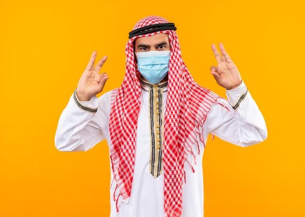 Uomo d'affari arabo in abbigliamento tradizionale e maschera protettiva per il viso con espressione sicura che fa il gesto di meditazione con le dita in piedi sopra la parete arancione