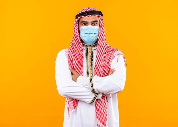 Uomo d'affari arabo in abbigliamento tradizionale e maschera protettiva per il viso con espressione fiduciosa in piedi sopra la parete arancione