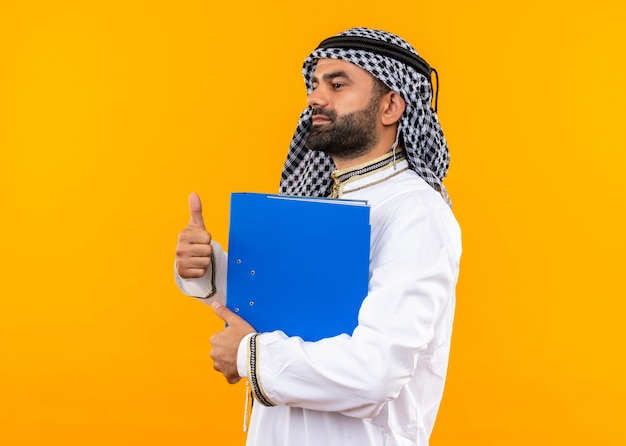 Uomo d'affari arabo nell'usura tradizionale che tiene cartella blu che mostra i pollici in su in piedi lateralmente sopra la parete arancione