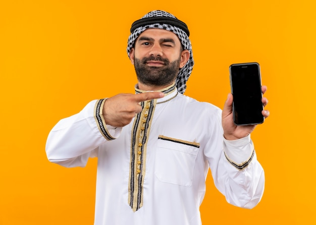 Arabic businessman in traditional wear holding smartphone pointing with finger to it looking confident winking standing over orange wall