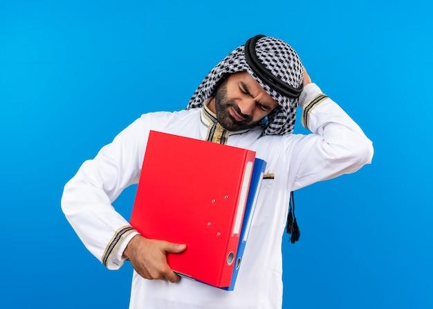 Uomo d'affari arabo nell'usura tradizionale che tiene due cartelle che sembrano in piedi confusi e molto ansiosi sopra la parete blu