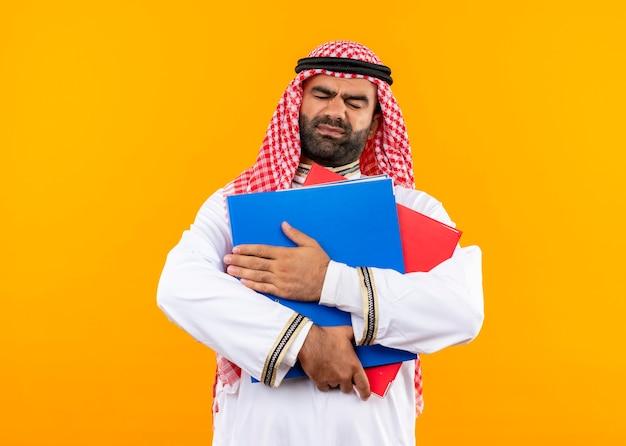 Uomo d'affari arabo nell'usura tradizionale che tiene due cartelle che sembrano dispiaciute e infelici in piedi sopra la parete arancione