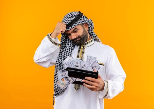 Uomo d'affari arabo nell'usura tradizionale che tiene portafoglio con contanti che sembra confuso e molto ansioso in piedi sopra la parete arancione