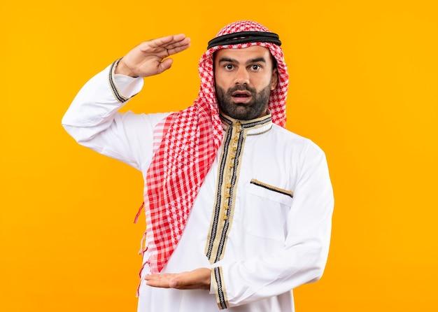 Uomo d'affari arabo nell'usura tradizionale che sembra sorpreso che mostra il gesto di grandi dimensioni, simbolo di misura che sta sopra la parete arancione