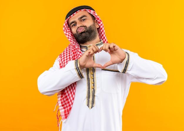 Uomo d'affari arabo nell'usura tradizionale che fa il gesto del cuore con le dita sul petto cercando di dare un bacio in piedi sopra la parete arancione
