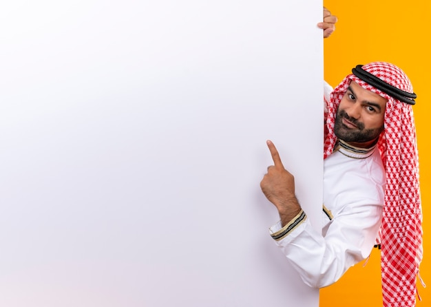 Arabic businessman in traditional wear peeking out blank billboard pointing with finger at it smiling standing over orange wall