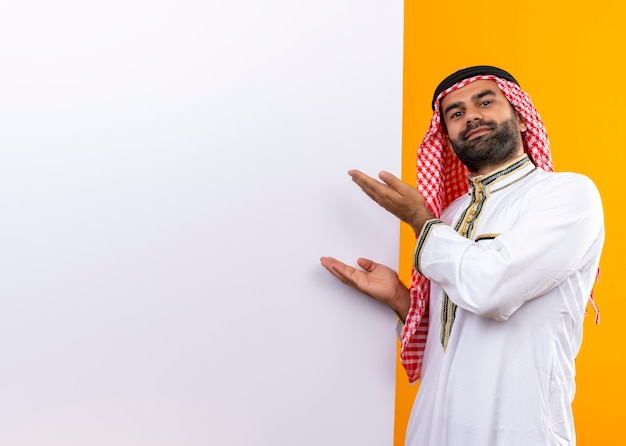 Arabic businessman in traditional wear presenting with arms blank billboard standing over orange wall