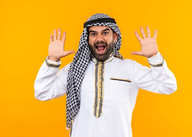 Arabic businessman in traditional wear raising hands in surrender looking surprised standing over orange wall