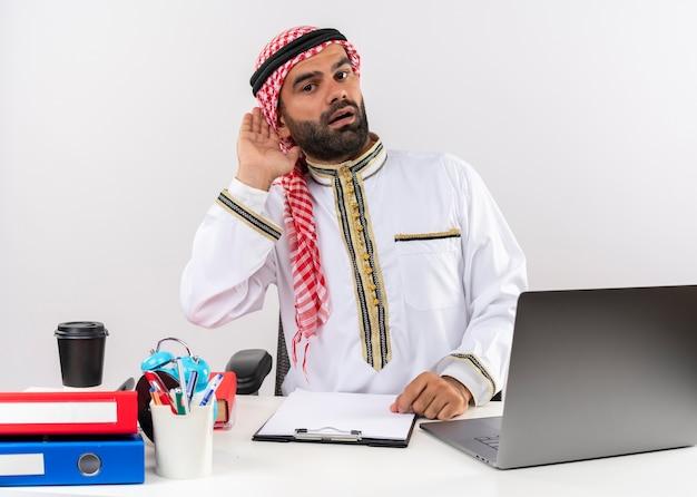 Uomo d'affari arabo nell'usura tradizionale che si siede al tavolo con il computer portatile che tiene la mano vicino all'orecchio cercando di ascoltare lavorando in ufficio