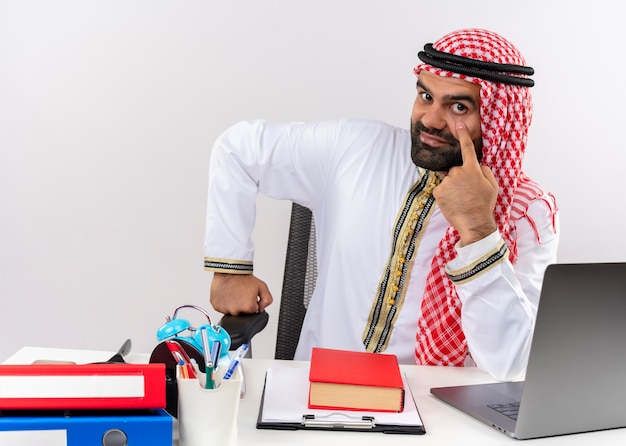 Arabic businessman in traditional wear sitting at the table with laptop computerpointing with finger to his eye waiting for payment working in office