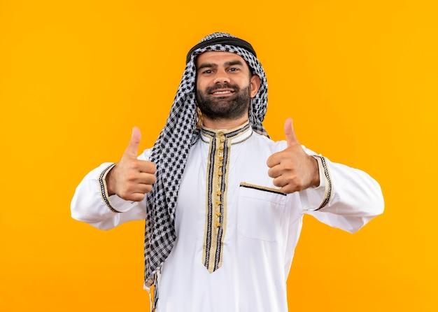 Uomo d'affari arabo nell'usura tradizionale sorridente fiducioso che mostra i pollici in su in piedi sopra la parete arancione