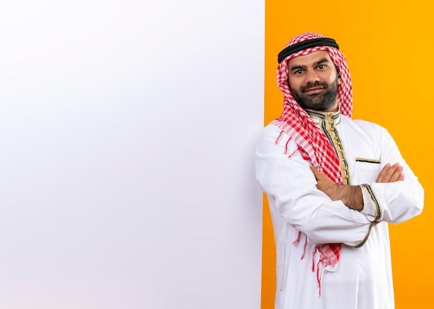 Uomo d'affari arabo nell'usura tradizionale in piedi vicino a bilboard vuoto con un sorriso sicuro sul viso sopra la parete arancione