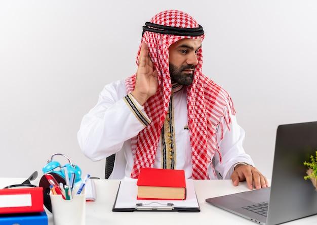 Uomo d'affari arabo nell'usura tradizionale che lavora con il computer portatile che tiene la mano al suo orecchio cercando di ascoltare seduto al tavolo in ufficio