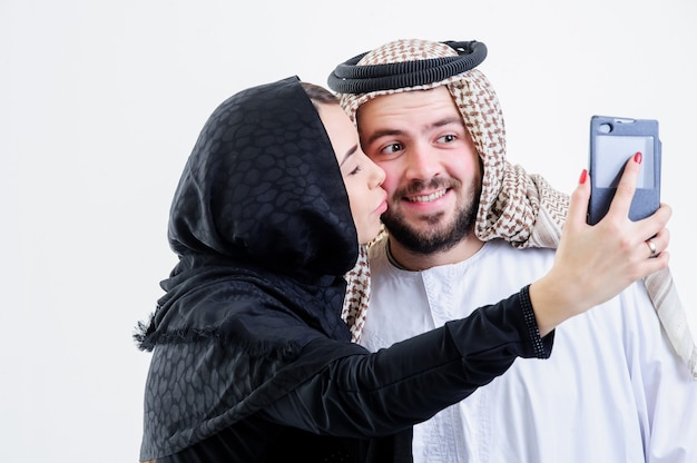 Arabic couple take self pictures with sell phone.selfie.