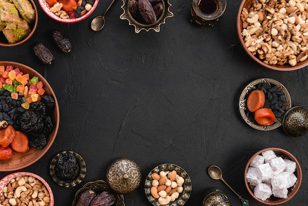 Арабские вкусные сухофрукты; орехи; лукум; пахлава на черном фоне
