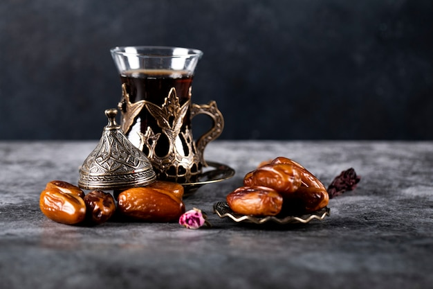アラビア語の喜びは、黒のお茶のグラスと暗い大理石に日付