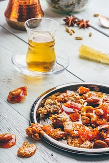 Арабские лакомства с разными орехами и семечками на металлической тарелке с травяным чаем в восточном бокале