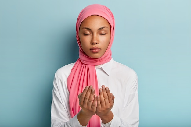 Arabic faithful dark skinned woman keeps hands in praying gesture, asks allah for good health, believes in wellness has veiled head, wears white shirt keeps eyes closed enjoys peaceful atmosphere