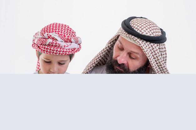 白いポスターを保持し、舌を突き出して息子とアラビア語の父ストックフォト