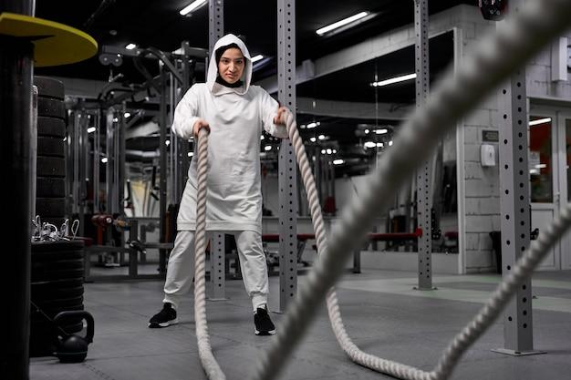 スポーツのヒジャーブを身に着けて、バトルロープでクロスフィットトレーニングをしているアラビアの女性アスリート。定期的なスポーツは免疫システムを高め、健康を促進します。健康的な生活様式