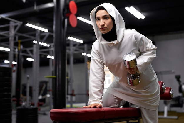 アラビアの女性はジムでダンベルを使用してトレーニングエクササイズを行い、白いスポーティーなヒジャーブウェアスタンドで強い若いフィットのイスラム教徒の女性がエクササイズに集中している側を見て