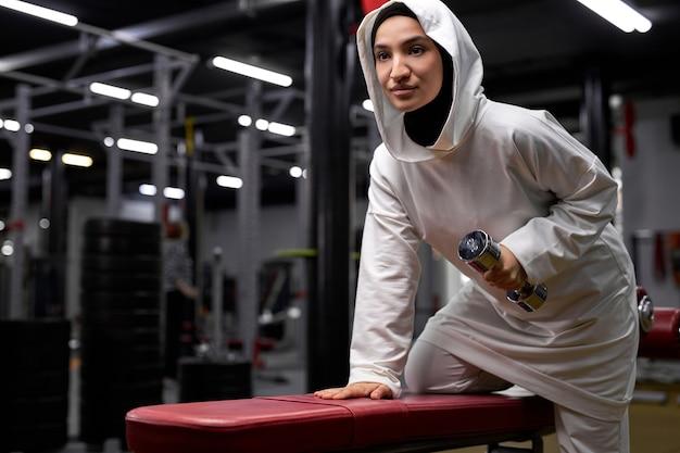 アラビアの女性はジムでダンベルを使用してトレーニングエクササイズを行い、白いスポーティーなヒジャーブウェアスタンドで若いフィットのイスラム教徒の女性がエクササイズに集中している側を見て