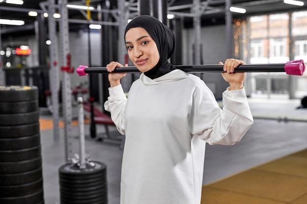 Арабская женщина в спортивной мусульманской одежде позирует, держа в руках штангу, имея красивый вид. в современном тренажерном зале