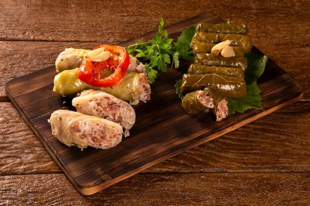 Арабская еда. аппетитные голубцы и рис и мята, завернутые в листья виноградной лозы на деревянном фоне.